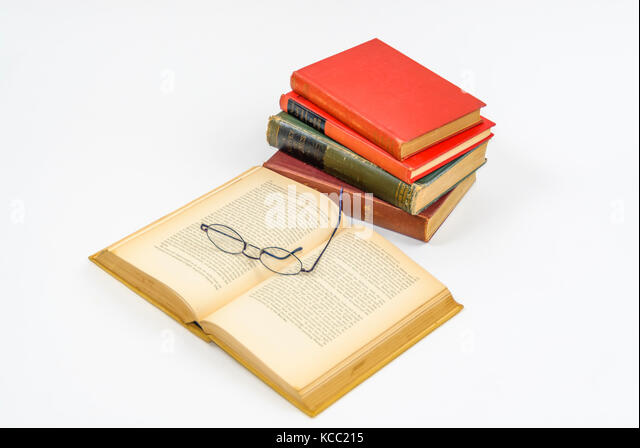 Open book isolated on white table with a stack of books and reading glasses. - Stock Image