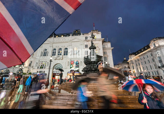People with Umbrellas at Piccadilly Circus at night, London, UK - Stock Image