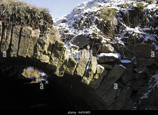 Arched remains of stone conduit built over the Cheesden Brook at site of former Croston Close - Stock Image