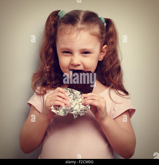 Cunning kid girl eating dark chocolate with pleasure and curious look. Vintage closeup portrait - Stock Image