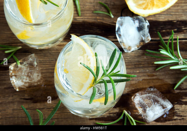Alcoholic drink (gin tonic cocktail) with lemon, rosemary and ice on rustic wooden table, copy space - Stock Image