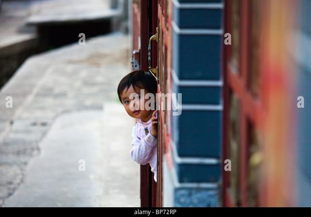 Young chinese girl peeking around a corner in Dali, Yunnan Province, China - Stock Image
