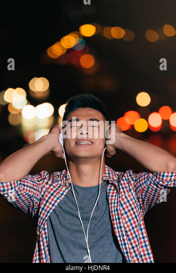 Portrait of a asian young man listening music with headphones in the city. - Stock Image