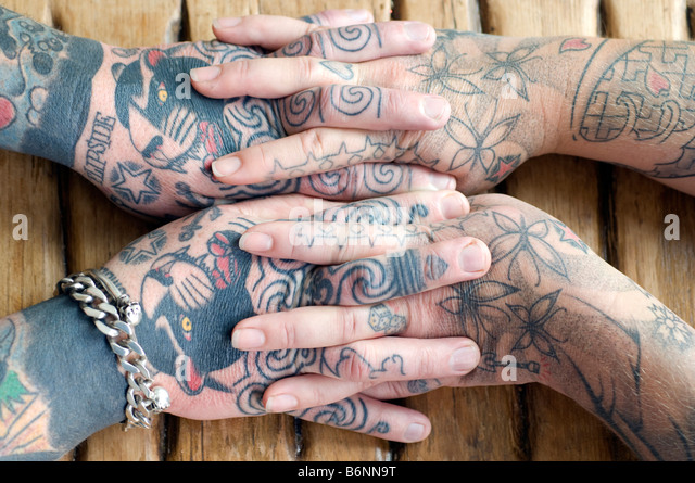 The entwined hands of a married couple who both have extensive tattoos - Stock-Bilder