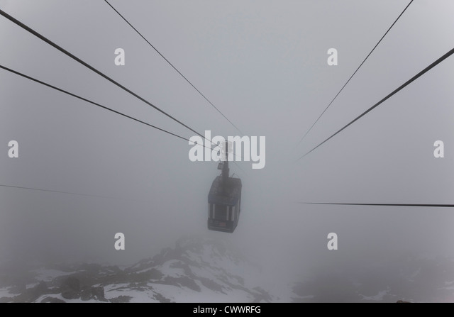 Ski lift on wires in fog - Stock Image