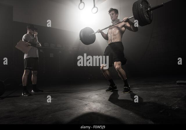 Mid adult man lifting barbell, while trainer looks on, low angle view - Stock Image
