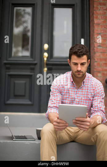 Man sitting on step using digital tablet - Stock Image