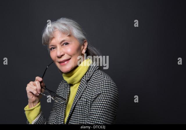 Studio portrait of wise senior woman holding spectacles - Stock Image
