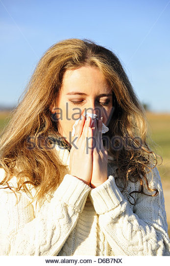 Woman blowing her nose outdoors - Stock Image