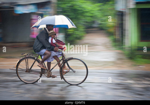 CYCLIST FATHER AND DAUGHTER IN SIGIRIYA DURING MONSOON RAIN STORM - Stock Image