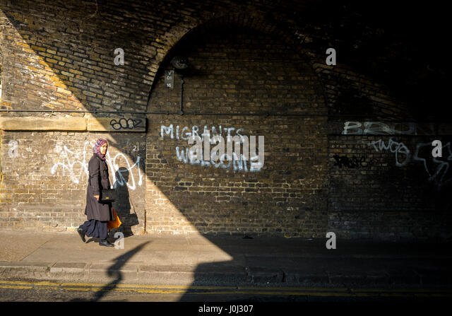 Asian woman walks past graffiti in London's Bethnal Green welcoming migrants. - Stock Image