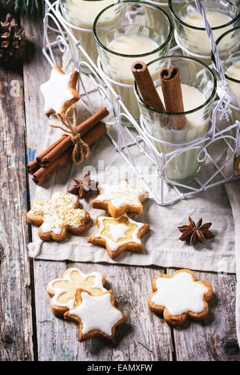 Christmas cookies assorted and glasses of milk cocktail, served with cinnamon sticks. - Stock Image