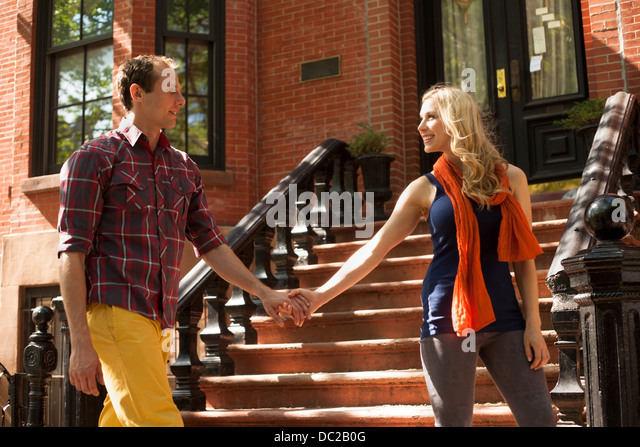 Couple walking hand in hand past outdoor stairs - Stock-Bilder