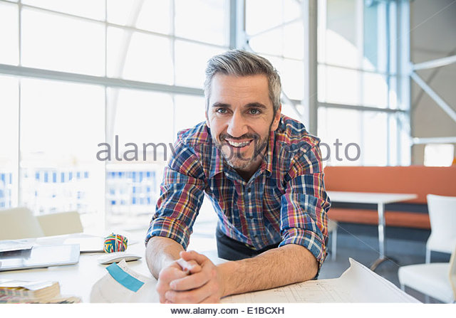 Smiling creative businessman in office - Stock Image