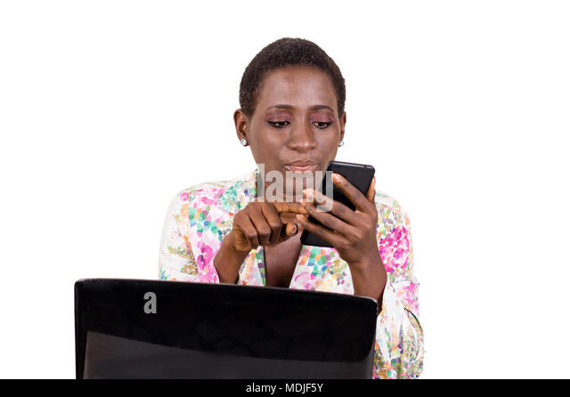 Young business woman sitting in front of a laptop consults his mobile phone isolated on white background - Stock Image