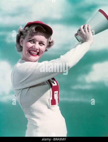 1940s 1950s SMILING TEEN GIRL CHEERLEADER WEARING VARSITY LETTER SWEATER HOLDING MEGAPHONE - Stock Image