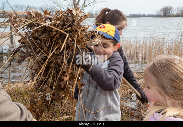 Detroit, Michigan - A Cub Scout volunteer helps clean Belle Isle, a state park on an island in the Detroit River. - Stock Image