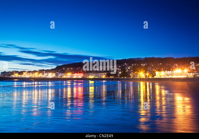 Twilight over Weston-Super-Mare, Somerset, England, UK with the lights of the town reflected in the wet sand at - Stock-Bilder