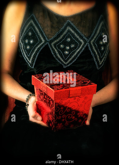 A cropped woman in a period dress holding a fancy red gift box - Stock-Bilder
