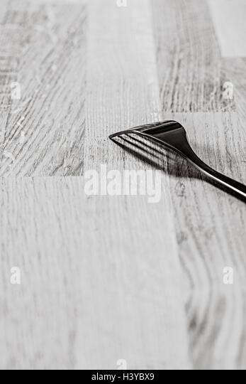 Single fork on wooden table. Black and white kitchen still life. - Stock-Bilder
