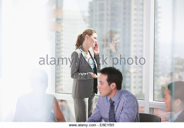 Businesswoman talking on cell phone in meeting - Stock-Bilder