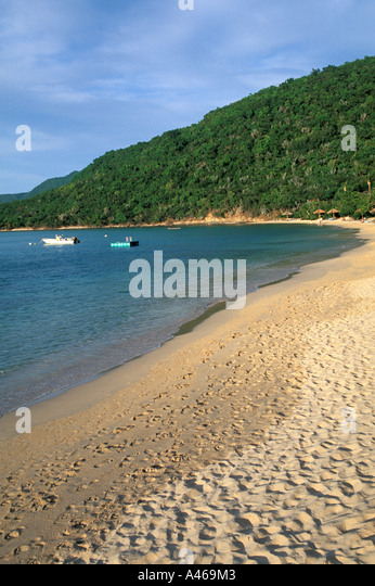 British Virgin Islands BVI Virgin Gorda Little Dix Bay deserted  beach footsteps fishing boats background seascape - Stock Image