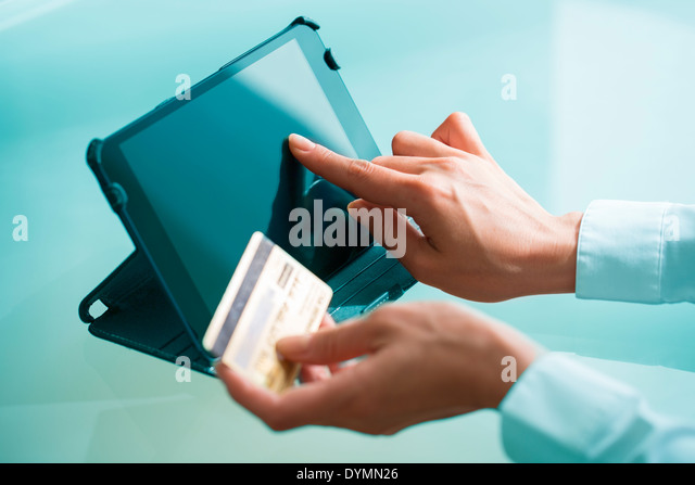 Woman shopping on internet using tablet pc and credit card - Stock Image
