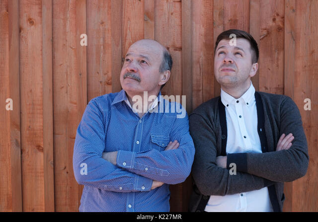 The father and the adult son are standing by the wooden wall and looking thoughtfully upward. - Stock Image
