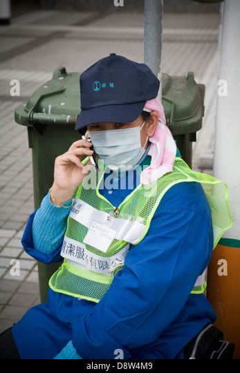 Woman street-cleaner wearing a cap, dust coat, high-visibility safety vest, and dust mask, talking on mobile phone, - Stock Image