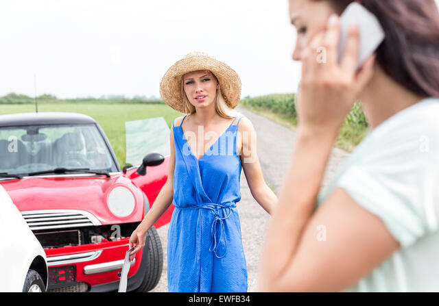 Angry woman looking at female using cell phone by damaged cars on road - Stock Image