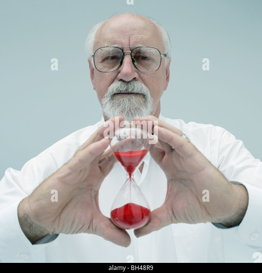 A senior man holding a glass egg timer with a serious expression - Stock Image