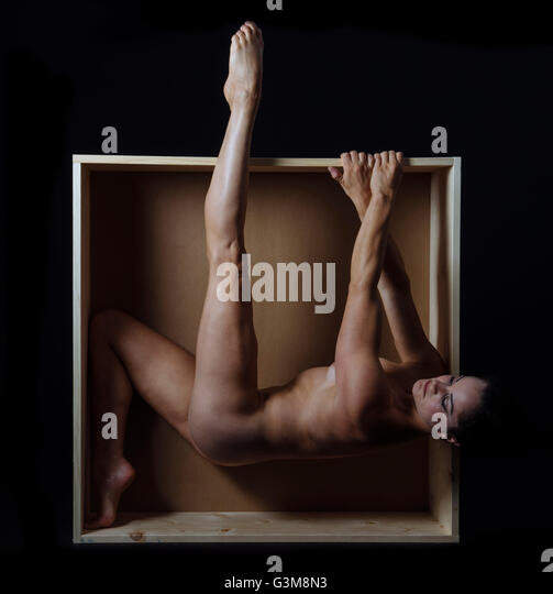 Naked woman hanging from edge of box - Stock Image