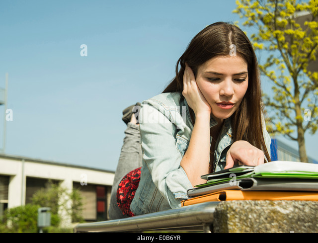 Brunette young woman lying on bench using digital tablet - Stock Image