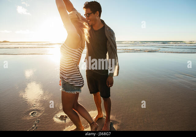 Shot of loving young couple dancing on the beach on a summer day. Young man and woman dancing on the seashore. - Stock Image