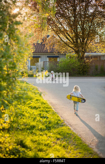 Sweden, Vastergotland, Lerum, Girl (6-7) walking to boy (8-9) with skateboard - Stock Image