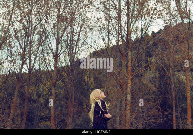 Young woman hugging herself in a forest - Stock Image