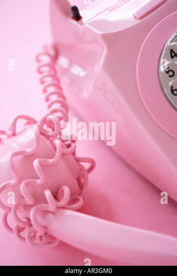 Cable wrapped around pink telephone receiver on pink background - Stock Image