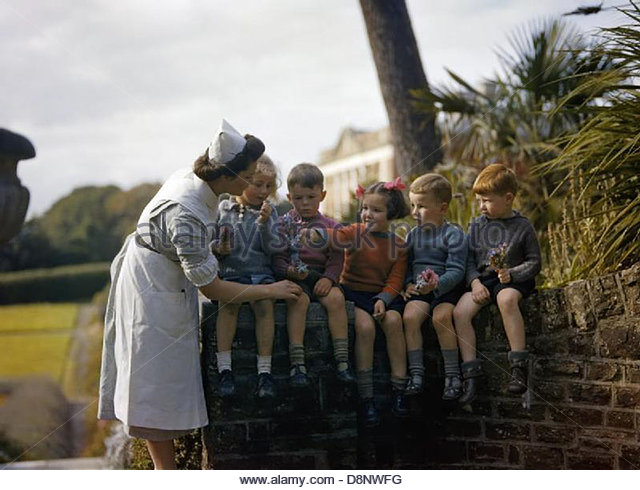 A nurse with child evacuees from Plymouth in the garden of the Chaim Weizmann Home at Tapley Park, Instow, North - Stock-Bilder