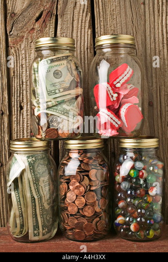 Jars full of money and teeth - Stock Image