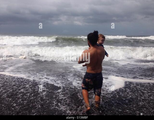 Paternal love, Father with baby enjoying the Waves at the pacífico sea un Guatemala - Stock Image