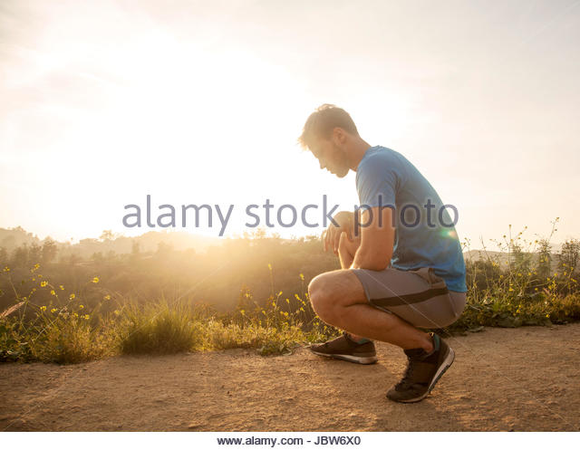 Young man outdoors, wearing sports clothing, crouching, taking a break from workout - Stock-Bilder