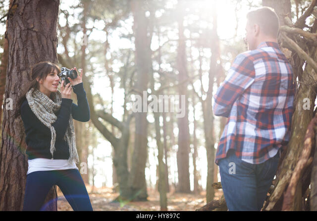 A woman takes a photo of her male companion as they walk in the woods - Stock Image