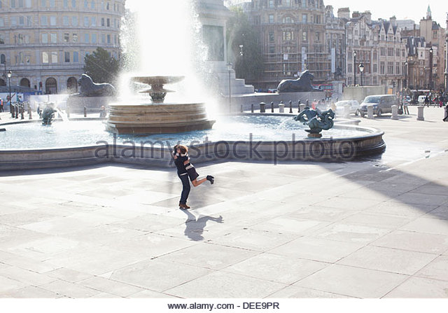Man lifting woman in front of urban fountain - Stock-Bilder