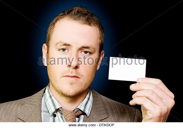Door to door salesman holding up a business card to identify himself and the company he represents as he goes from - Stock Image