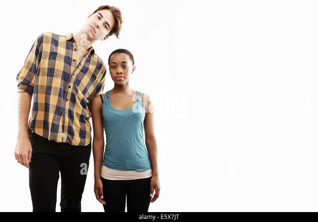 Studio portrait showing contrasting height of young couple - Stock Image
