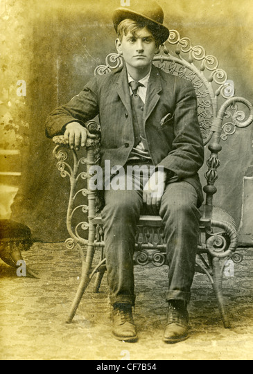 Boy sitting in chair wearing suit and bowler hat during late 1800s or early 1900s fashion chair furniture well dressed - Stock-Bilder