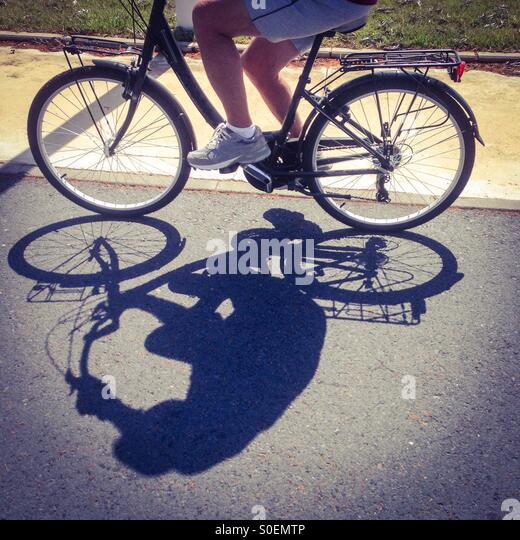Cyclist and shadow - Stock-Bilder