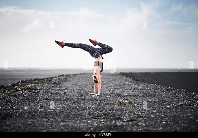 Young women doing a handstand on a deserted unmade road in Southern Iceland - Stock Image