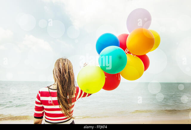 Woman with colorful Balloons on the beach,Outdoors lifestyle filters image - Stock Image