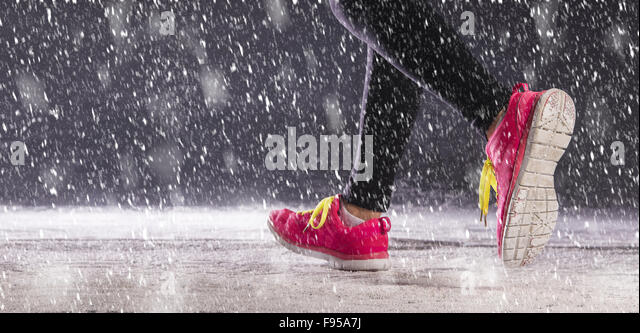 Athlete woman is running during winter training outside in cold snow weather. - Stock Image